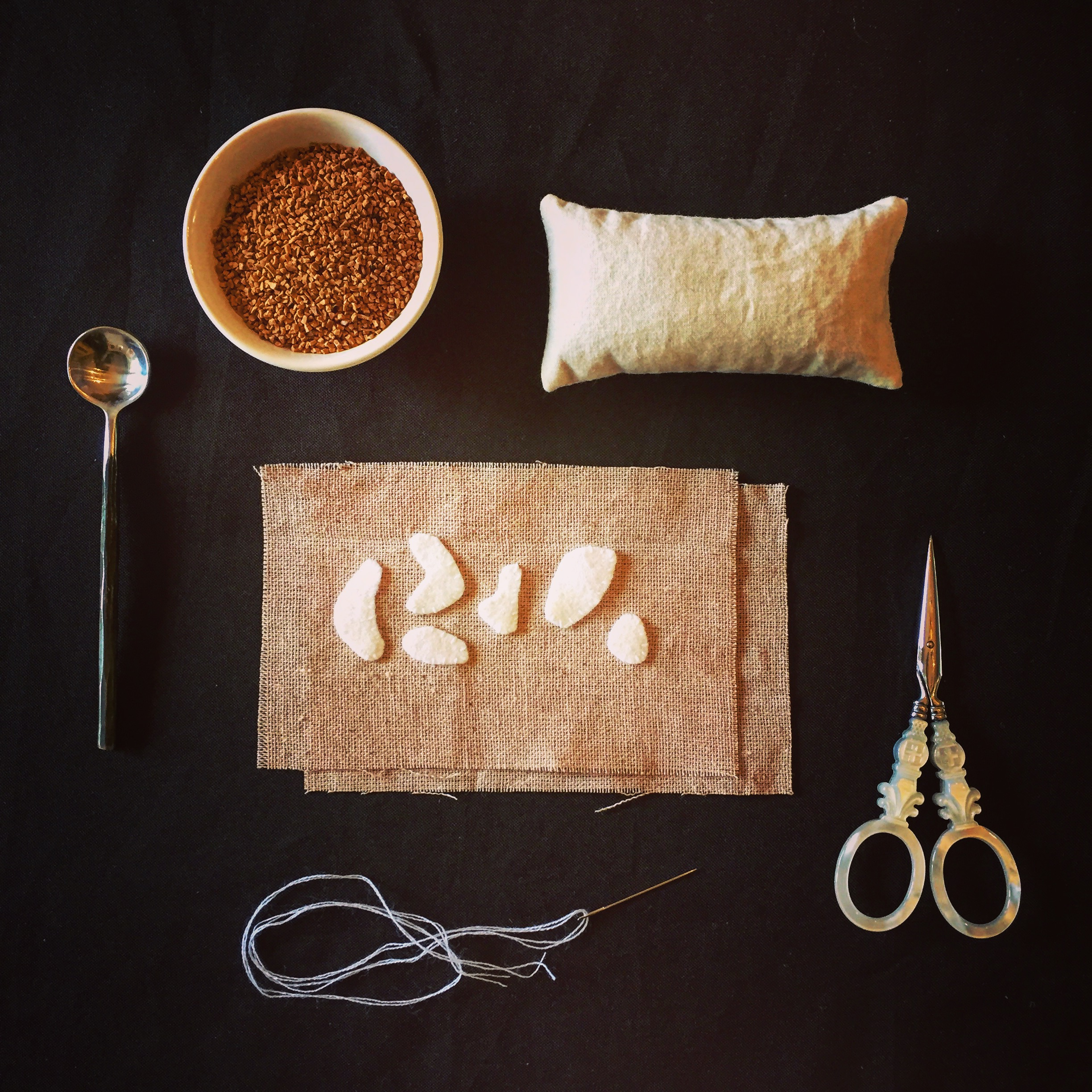 wool appliqué on osnaburg with muslin pouch filled with walnut shells